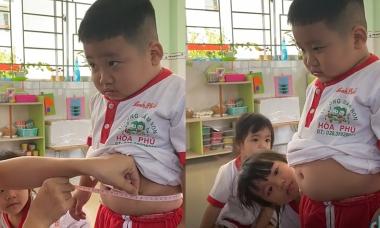 Cậu bé hóp bụng, nín thở khi bị cô giáo đo vòng eo